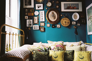A gallery wall of small artworks above a bed with striped bedding