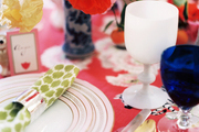 A table set with green patterned napkins and a mixture of flatware and glassware