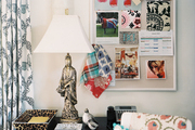 An inspiration board of images and fabric samples beside a gold chinoiserie lamp