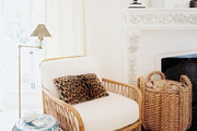 A natural fiber rug, a blue-and-white garden stool, and a leopard-print pillow in the corner of a living space