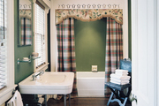 Green walls and plaid shower curtains in a guest bath