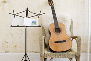 A sheepskin-covered wicker chair with a guitar and music stand and a Beni Ourain–style rug