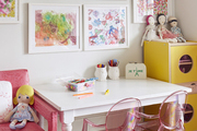 White and pink decor in wood floored children's room.