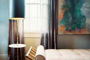 A daybed beside a gold floor lamp with a black lampshade