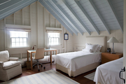 Twin beds under blue ceiling beams in white walled bedroom.