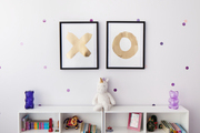 Symmetrical framed art and bookshelves in front of a dotted white wall.