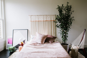 This bed is surrounded by art, plants, and a statement wall hanging.