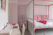 A contemporary pink kids' room with canopy bed