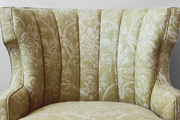 An armchair with channel-back detailing covered in Bella fabric by Elizabeth Benefield