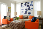 Orange accent furniture and large scale art in a window-lit living area.