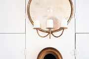 A round candle sconce above a wooden mirror