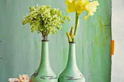A pair of vases on a green bench