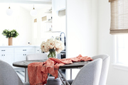 A dining room with gray upholstered chairs. and a modern black pendant lamp.
