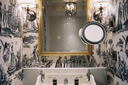 Black-and-white toile wallpaper and a pair of sconces with white shades