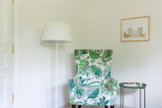 A green and white chair in the corner of a room with white walls.