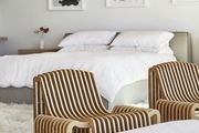 """I love to lay in bed and open the doors on the balcony and let the beach air wash over us,"" says the Lunya founder, of her gorgeously light master bedroom. Custom Bed; Custom Shelving; Taschen Book; Garmentory Assorted Accent Pieces; Maaari Ceramics; Vintage Armchairs; Karina Bania Artwork via Uprise Art; Restoration Hardware Bedding; Living Fivani Ottomans."