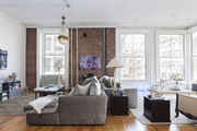 Tall windows and accenting brick wall in open living area.