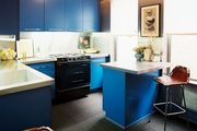 Blue cabinets and stainless steel countertops paired with a leather bar stool