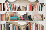 A white cabinet filled with books and decorative objects