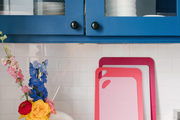 A kitchen counter with bold colored cutting boards, coffee mugs, a spoon holder, and an abstract vase sitting on top.