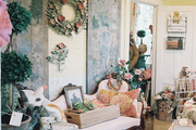 A white upholstered settee in a room filled with garden accessories
