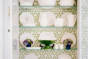 A china cabinet backed with geometric green wallpaper