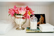 A trophy cup of flowers and a tray of bath essentials on white shelves