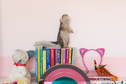 Decorative items on a white dresser in a kid's room with pink striped walls.