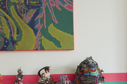 An abstract artwork above a vignette of figurines and clown hats atop a radiator in a Paris apartment