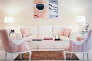A pair of vintage pink chairs paired with a white couch