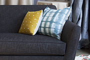 A sofa—with Rebecca Atwood and Cotton & Flax thow pillows—sits on a Berber-inspired West Elm rug
