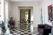 A sculptural brass accent table atop marbled floors in an entry way