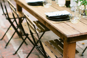 A rustic dining table and chairs for a festive summer dinner party.