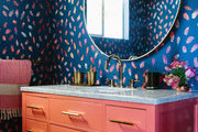 A bathroom with blue and pink wallpaper.