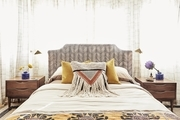 A fringe throw pillow that accents the bedroom's comforter.