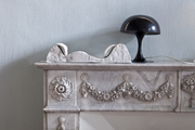 A gray and white marble fireplace mantel with a modern black lamp and a sculpture.