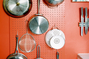 Pots and colanders hung from hooks on a red pegboard wall
