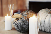Candles and pumpkins atop a dining table
