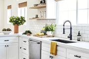 A white kitchen with patterned floor tiles and area runner.