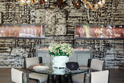 A large-scale relief wall design by Peter Lane behind a scuptural chandelier and dining area