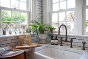 A farmhouse sink in the corner of a kitchen space