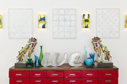 A pair of antique foo dogs and vintage letters on a red console under midcentury sconces and minimalist artwork