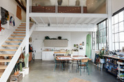A view of a dining space and kitchen in an airy loft.