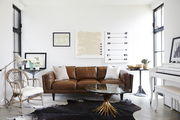 A music room with a vintage leather sofa, cowhide rug, rattan chair, and piano painted in a chalk white