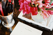 Flowers, stationery, and a cup of pens on a wooden desk