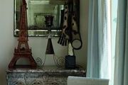 A metal chair, an antique mirror, and a table lamp