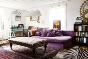 A purple couch and layered rugs in a living space