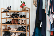 A detail of a shoe rack and clothing rack on a faux sheepskin rug.