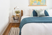 White and blue contemporary and bohemian bedroom with map wall decor.