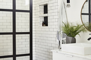 A bathroom with black and white tile, a marble counter top, and a circular mirror.